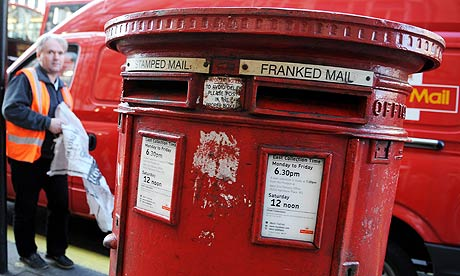 A Royal Mail worker collects mail from a postbox in London