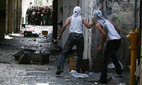 Palestinian youths hurl stones towards Israeli riot police during clashes in Jerusalem's Old City.