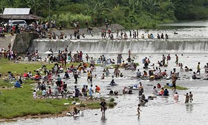 Earthquake survivors gather at a river as their main source of water in Padang, Indonesia