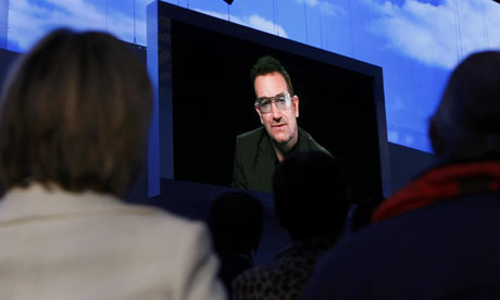 Delegates watch singer Bono address the Conservative conference in Manchester via video link