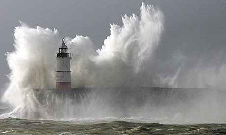 Huge waves break over the lighthouse on Newhaven harbour