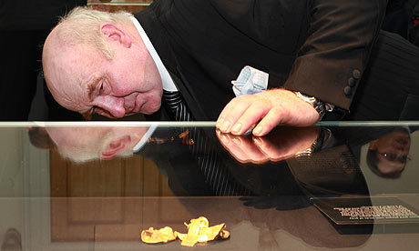 Farmer Fred Johnson inspects a gold piece found on his land, at the British Museum