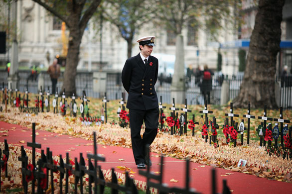 Remembrance Sunday: A man walks through Remembrance crosses for servicemen at Westminster Abbey