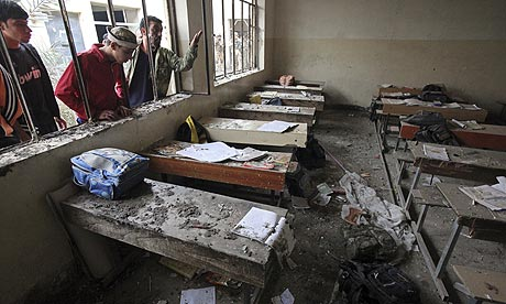 People inspect a classroom damaged in an explosion outside a school in Baghdad