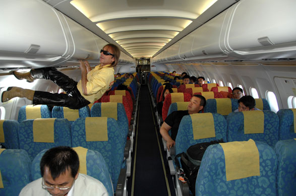 Alain Robert: Alain Robert climbs on the baggage racks of a Dragon Air plane