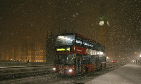 A bus goes past the House of Commons as it crosses Westminister Bridge during a snow fall