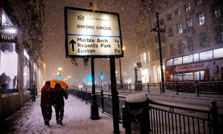 People braving the heavy snow in central London early this morning