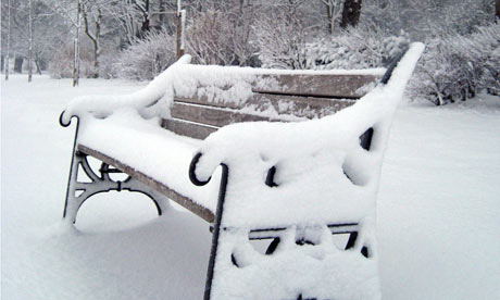 A park bench covered in snow in Finsbury Park, north London