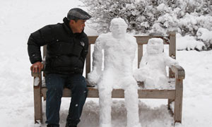 A man sits on a park bench with two snowmen in St. James's Park in central London