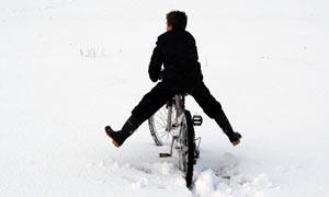 A boy cycles through the snow