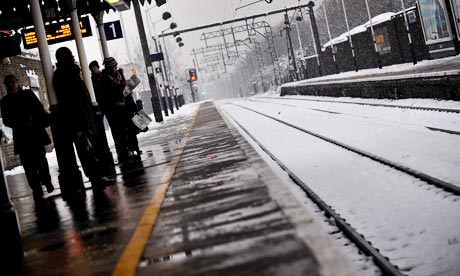 Commuters wait for a train in London after heavy snow fell across large parts of the UK