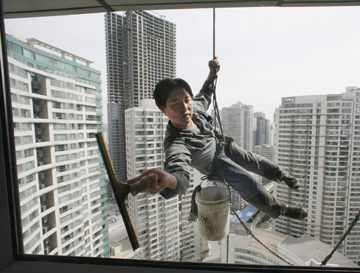Gallery China property market: A worker cleans the windows of an apartment block