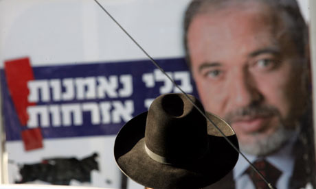 An ultra-orthodox Israeli stands in front of an Avigdor Lieberman election poster