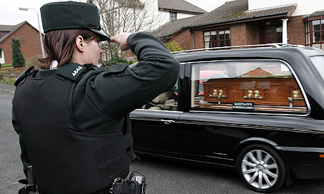 A Police Service of Northern Ireland officer salutes the coffin of Constable Stephen Carroll