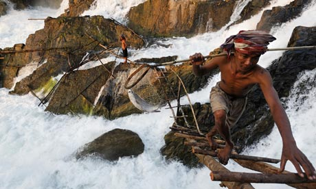 Mapping the Mekong River : A Lao fisherman harvesting fish from the powerful Khong falls