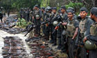 Sri Lankan troops inspecting weapons and dead bodies of Tamil Tiger rebels