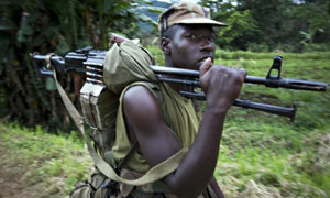 A Rwandan soldier carries his weapon through the village of Pinga in eastern Congo