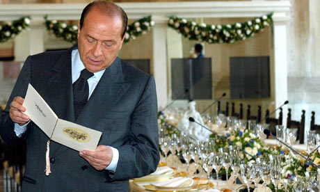 Silvio Berlusconi reads a lunch menu