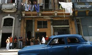 A vintage car passes a building on a street in Havana, Cuba