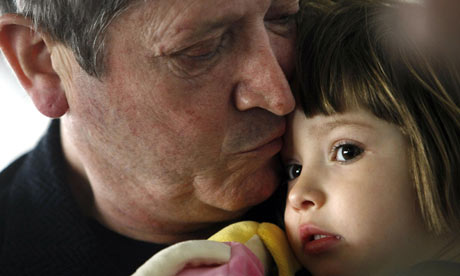 Jean-Michel André holds his daughter, Elise, while waiting to board a plane at Budapest