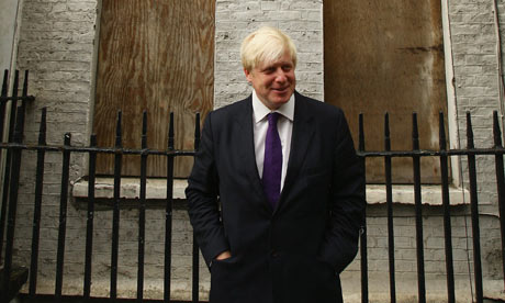 Boris Johnson standing in front of empty housing in London