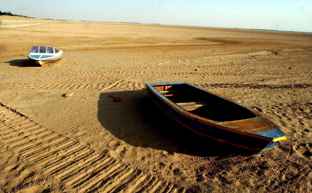 Minqin China: Boats rest . the bottom of a dried reservior oasis in China