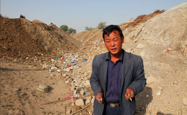 Minqin China: Huang at the bottom of a dried-up river that .ce ran past his his old home