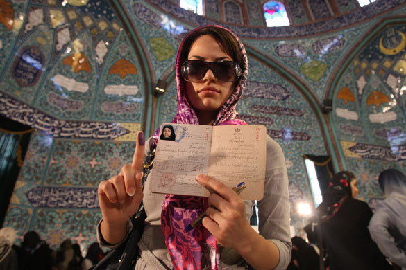Iraninan elections: A woman shows the ink on her finger after voting at a polling station