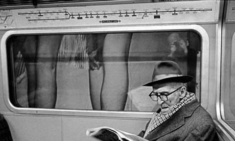 An older man reading a newspaper on a London underground tube train