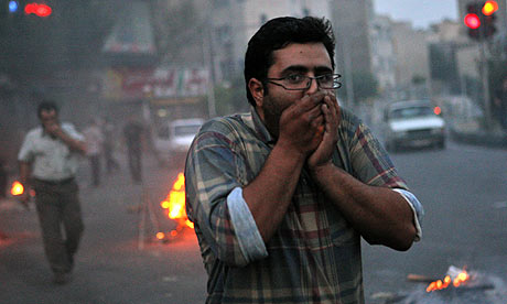 Iranian protesters cover their face from tear gas in Tehran