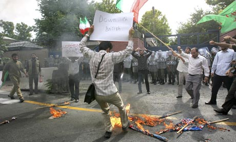 An Iranian protestor burns flags in front of British Embassy in Tehran, Iran