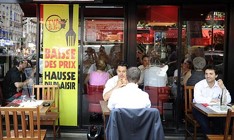 Customers have lunch near a sign which reads