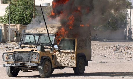 A British Army Land Rover burns near Moqtada al-Sadr's offices in Basra, Iraq, on 9 August 2004.