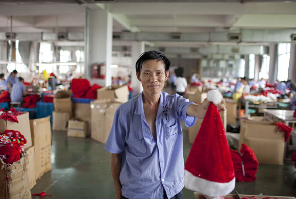Christmas production line: A worker holds up a Santa hat from the production line in Yiwu