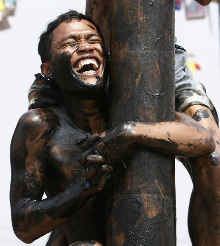 Jakarta independence day: A contestant laughs as he climbs a pole in an attempt to reach prizes