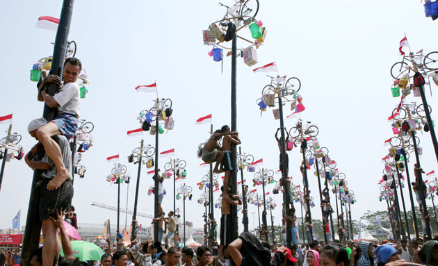 Jakarta independence day: Men climb greased poles to retrieve prizes like bicycles and rice cookers