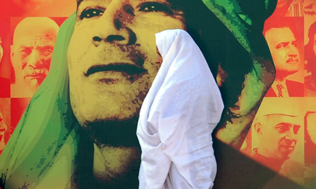 Woman walking poster of Muammar Gaddafi