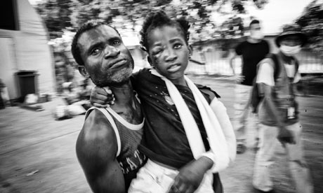 A man carries an injured child in Port-au-Prince, Haiti, six days after the earthquake.