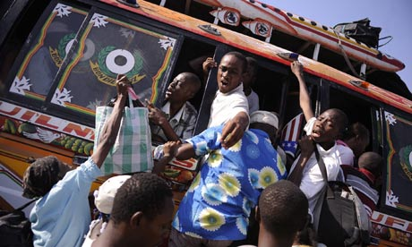 People climb onto departing buses in Port au Prince, Haiti