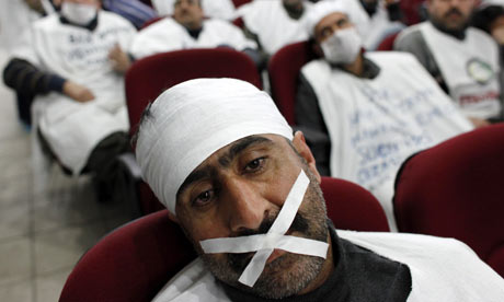 A man on hunger strike tapes his mouth during the protests over job and pay cuts