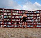 A beach goer selects books from world&#39;s longest outdoor bookcase on Bondi Beach, Sydney, Australia