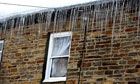A woman looks out of her window as large icicles hang down from the roof.