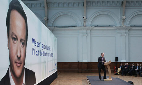 David Cameron speaks in front of a Conservative poster showing his own face.