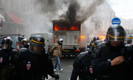 Riot police officers move back from a burning truck during clashes with youths in Lyon, France