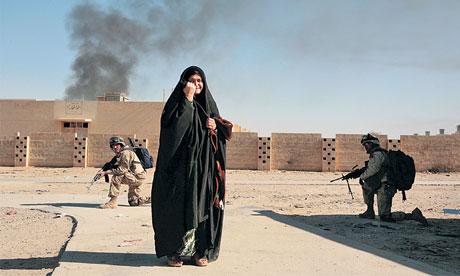US soldiers crouch behind an Iraqi woman in Ubaydi in November 2005