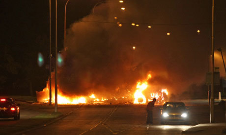 A burning bus blocks the road in Newtownabbey, Northern Ireland