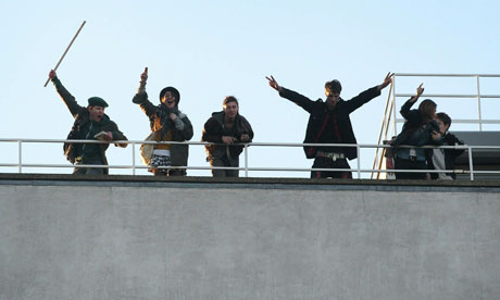 Student protesters wave from the roof of 30 Millbank,  home of Conservative Party headquaters
