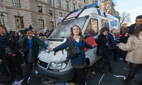 Schoolgirls join hands to peacefully stop attacks on a police van during student protests in London.