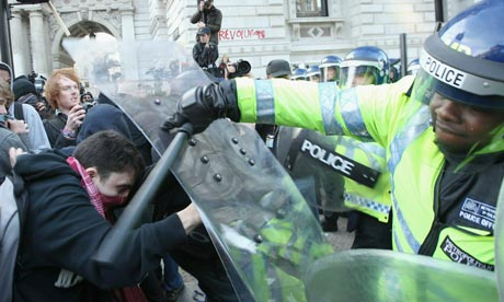 Police hold protesters back during a demonstration against tuition fee rises and funding cuts