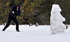 A Parks Police officer takes photographs of a snowman in Richmond Park in south west London